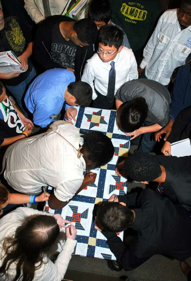 Students at Hamden Middle School sign a quilt after a veterans program at the school on Thursday. The quilt was made by Jane Dougherty of Branford for the Quilts of Valor Foundation and will be given to a wounded veteran. Arnold Gold/Register