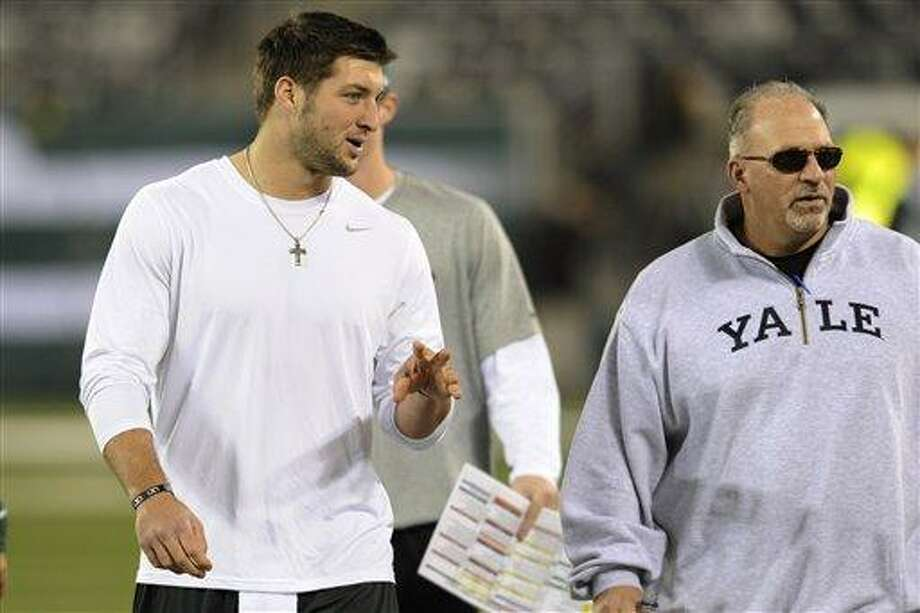 New York Jets quarterback Tim Tebow, center, walks the field with offensive coordinator Tony Sparano before an NFL football game against the New England Patriots Thursday, Nov. 22, 2012 in East Rutherford, N.J. (AP Photo/Bill Kostroun) Photo: AP / FR51951 AP