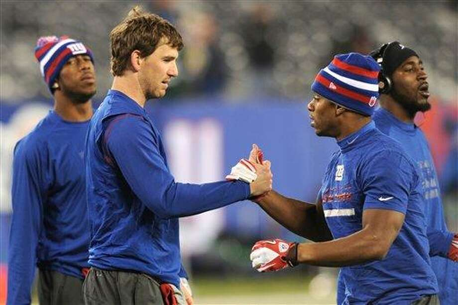 New York Giants quarterback Eli Manning, second from left, greets teammate Victor Cruz before an NFL football game against the Green Bay Packers Sunday, Nov. 25, 2012 in East Rutherford, N.J. (AP Photo/Bill Kostroun) Photo: AP / FR51951 AP