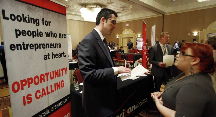 In this Oct. 4 photo, Blake Andrews with Verizon, left, visits with prospective employees during a job fair, in San Antonio. Employers advertised more jobs in September than at any other point in the past three years, a hopeful sign that job market is slowly improving. (AP Photo/Eric Gay) Photo: ASSOCIATED PRESS / AP2011