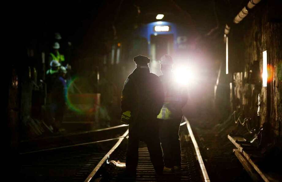 John Burkhard, right, assistant superintendent for the Way and Structures Division of the Port Authority Trans-Hudson train line, stands next to a police officer as a PATH train passes in the tunnel, Tuesday, Nov. 27, 2012, in Hoboken, N.J. While parts of the trans-Hudson service have gradually returned to operation since Superstorm Sandy, the Hoboken station has been closed, leaving thousands of commuters to seek alternatives. (AP Photo/Julio Cortez) Photo: ASSOCIATED PRESS / AP2012
