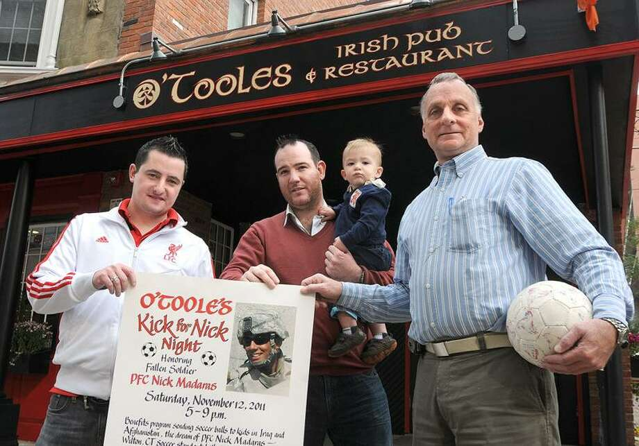 Peter Casolino/New Haven Register photo: Bill Madaras, right, father of fallen Army soldier, Nick Madaras, and the owners of O'Toole's Pub in New Haven, Colin O'Toole, left, and Damian Cashman, holding 1-year-old son, Luke Cashman, are putting on a fundraiser Saturday night in Nick's name. Nick was involved with helping Iraqi children before he was killed. In his name, thousands of soccer balls have been donated and sent to children in Iraq.