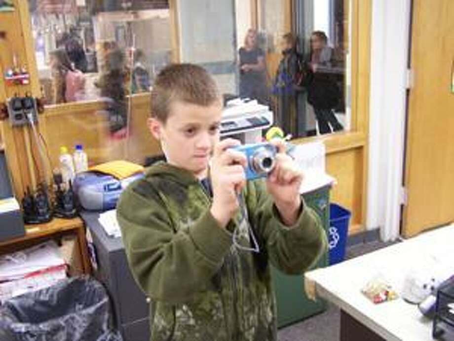 """Photo Courtesy W.A. WETTEL ELEMENTARY Fifth grader Daniel Faherty in his service position role as """"school photographer."""""""