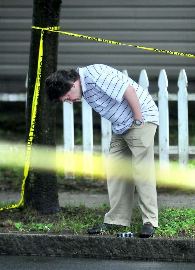 New Haven Police Detective Matthew Prinz investigates a shooting Monday on Bassett Street in New Haven. Arnold Gold/Register