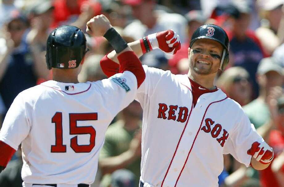 ASSOCIATED PRESS Boston Red Sox's Cody Ross, right, celebrates his three-run home run that also drove in Boston Red Sox's Dustin Pedroia (15) in the fourth inning of Sunday's game against the Atlanta Braves in Boston. The Red Sox won 9-4.