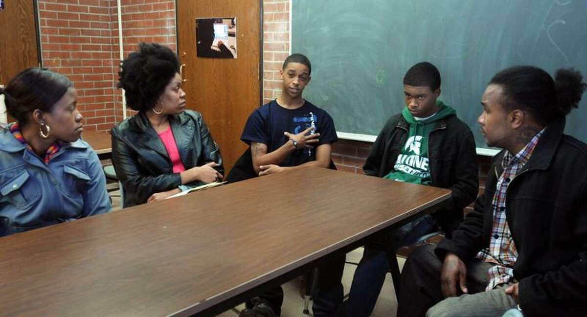 """From left, Speak Life! executive board member Hannah Joyner, Speak Life! leader Sheeva Williams-Nelson and her sons, Kenny, 19, and Josh Williams, 16, and Darrell Allick of """"Ice the Beef,"""" discuss efforts to reopen the """"Q"""" House at a meeting recently at Stetson Branch Library in New Haven. Melanie Stengel/Register"""