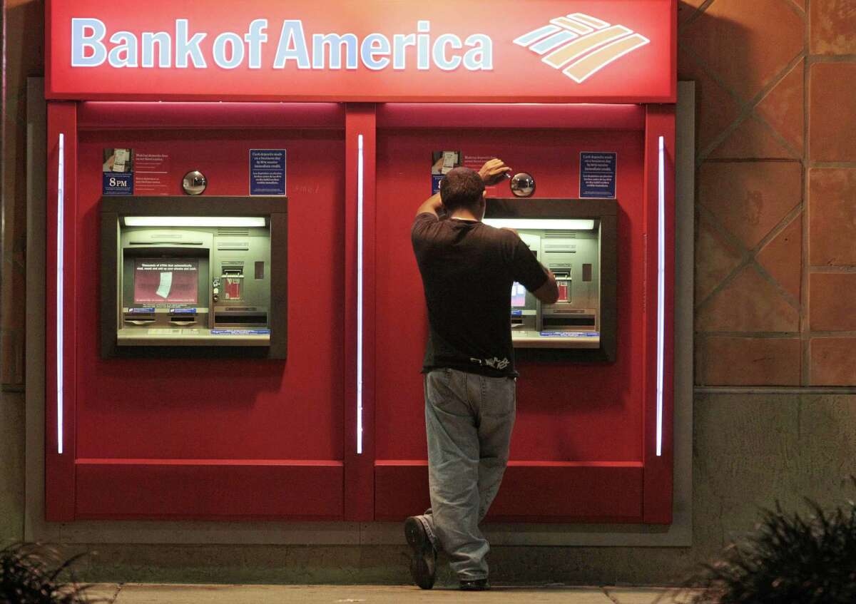 This photo taken Oct. 14 shows a customer at a Bank of America ATM in Hialeah, Fla. Bank of America Corp. is scrapping its plans to charge a $5 monthly debit card fee. The bank's decision to drop the fee came after a roar of customer outrage in recent weeks over the fee. (AP Photo/Alan Diaz)