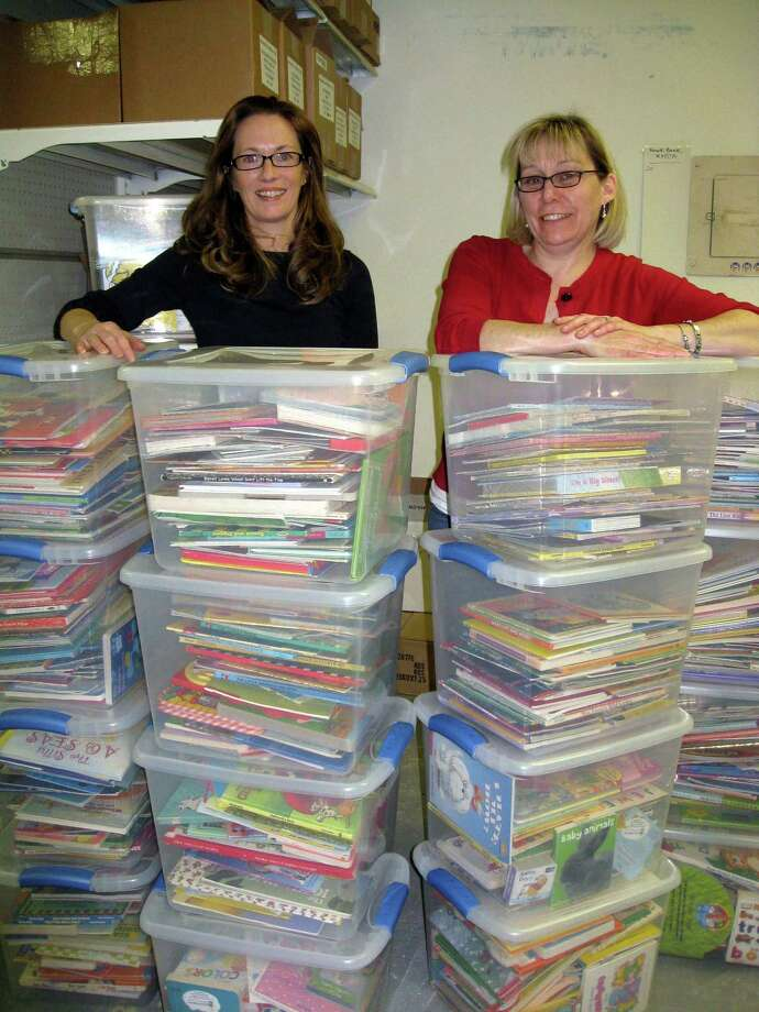 Sandi Kahn Shelton/Register photo, Bonnie Patten, left, and Linda Sylvester, Books for Kids coordinator at Read to Grow, look over boxes of 750 children's books which will go to the 13 Court Service Centers throughout the state and then be given to kids who go to court with their parents.