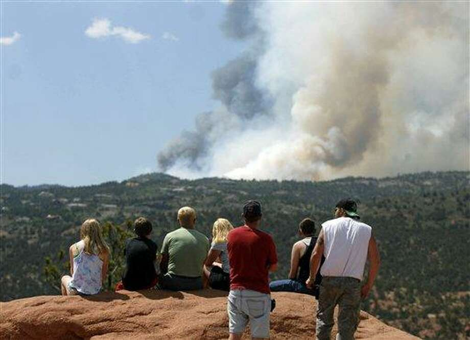 People watch Saturday as smoke billows from a wildfire west of Colorado Springs, Colo. Associated Press Photo: AP / FR81708 AP