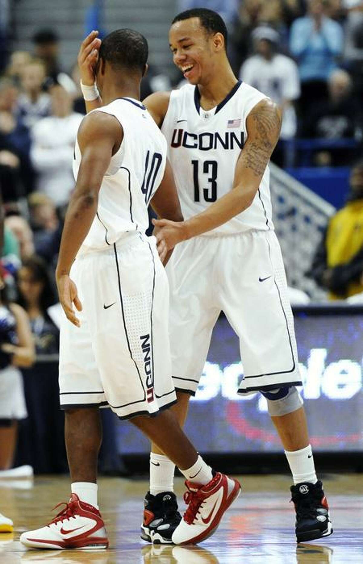 Connecticut's Shabazz Napier, right shares a moment with Connecticut's Ethan Waite, left, in the final minutes of an NCAA college basketball game against St. John's in Hartford, Conn., Saturday, Dec. 31, 2011. Connecticut won 83-69. (AP Photo/Jessica Hill)