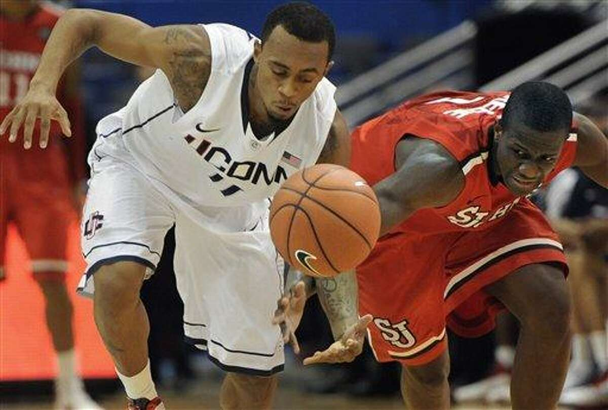 Connecticut's Ryan Boatright, left, steals the ball from St. John's Phil Greene, right, in the first half of an NCAA college basketball game in Hartford, Conn., Saturday, Dec. 31, 2011. (AP Photo/Jessica Hill)