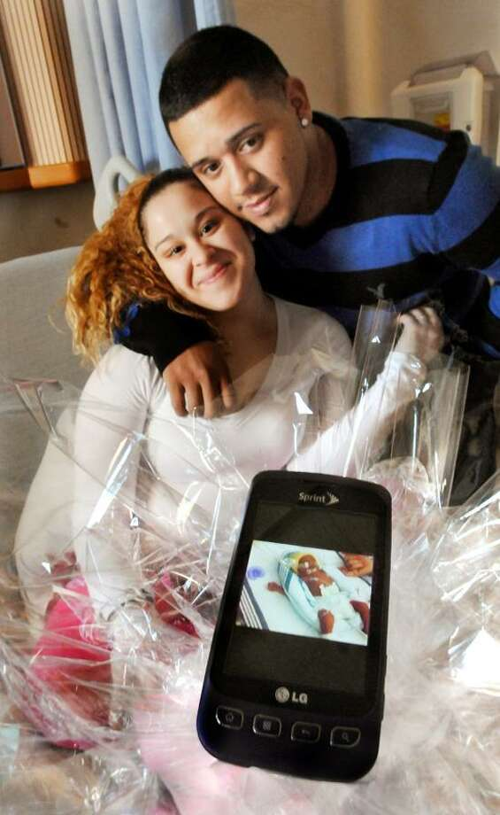 Lisette Baez and Elias Mendez Jr. with a cellphone picture of their daughter, Enaidalise. She was born at Yale-New Haven Hospital at 12:00:19 a.m. The family is from New Haven.     Melanie Stengel/Register