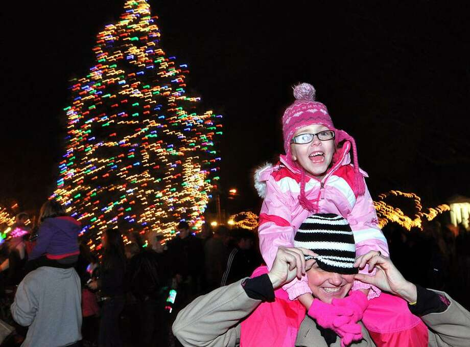 Riley Lapham, 5, pulls her mother's hat down as they were enjoying the Milford Tree Lighting Ceremony on the Green. They are from Milford.   Peter Casolino/New Haven Register