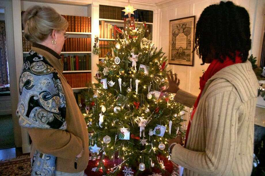 From left: Betty Harris of Old Saybrook gets a tour of the museum from tour guide Susan Robinson of Derby. Local garden clubs decorate the Osborne Homestead Museum and this year's theme displays a variety Christmas plants for each room.              Chynna Davis/For the Register