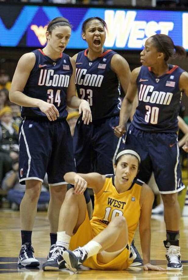 "Connecticut's Maya Moore, (23) celebrates with teammates Kelly Faris (34) and Lorin Dixon (30) after a turnover by West Virginia's Liz Repella (10) in the second half of an NCAA college basketball game in Morgantown, <a href=""http://W.Va"">W.Va</a>. on Tuesday, Feb. 8, 2011. Connecticut won 57-51. (AP Photo/David Smith) Photo: AP / FR93543 AP"