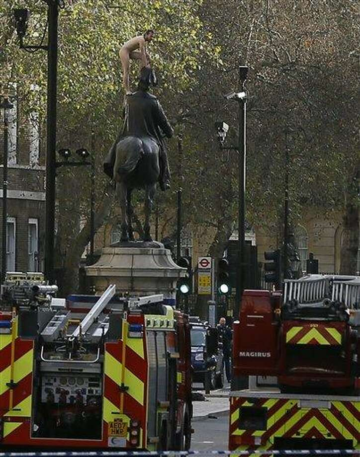 """EDS NOTE NUDITY A naked man stands on a statue of Prince George, Duke of Cambridge, on Whitehall in London,  Friday, Nov. 23, 2012. Police and eyewitnesses say a naked man has climbed atop an equestrian statue in the heart of Whitehall, London's government district. A Scotland Yard spokesman said that the man, believed to be in his 30s or 40s, has been sitting atop the statue for the better part of two hours. He said Friday: """"We're still talking to him. We're still trying to get him down without causing any injury to him.""""  (AP Photo/Kirsty Wigglesworth) Photo: AP / AP"""