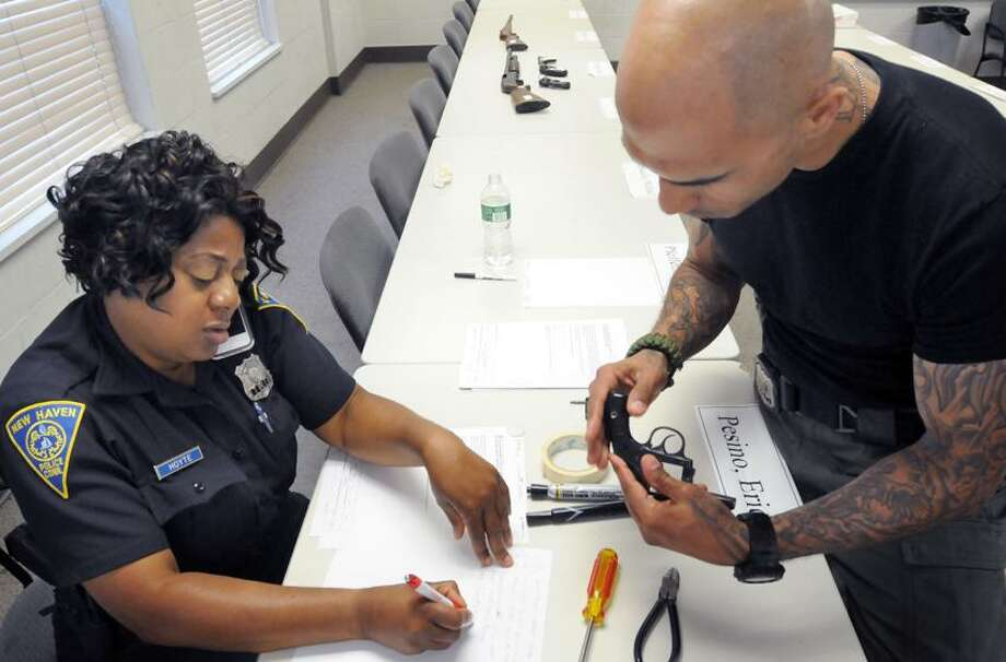The New Haven Police Department held a gun buy-back at the New Haven Police Academy. Officer Jacqueline Hoyte, left, logs in a gun while firearms instructor Officer Jason Salgado checks the gun over. Mara Lavitt/New Haven Register