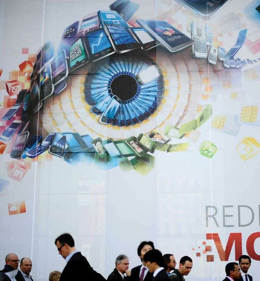 Participants attend the Mobile World Congress, the world's largest mobile phone trade show, in Barcelona, Spain, Monday. Associated Press Photo: ASSOCIATED PRESS / AP2012