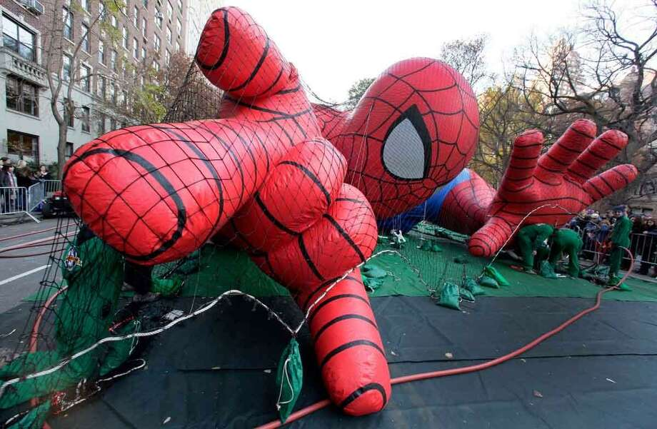 Workers inflate the Spider-Man balloon for the 86th annual Macy's Thanksgiving Day Parade, on New York's Upper West Side,  Wednesday, Nov. 21, 2012. More than 3 million people typically attend the event and it has a TV audience of 50 million. (AP Photo/Richard Drew) Photo: ASSOCIATED PRESS / AP2012