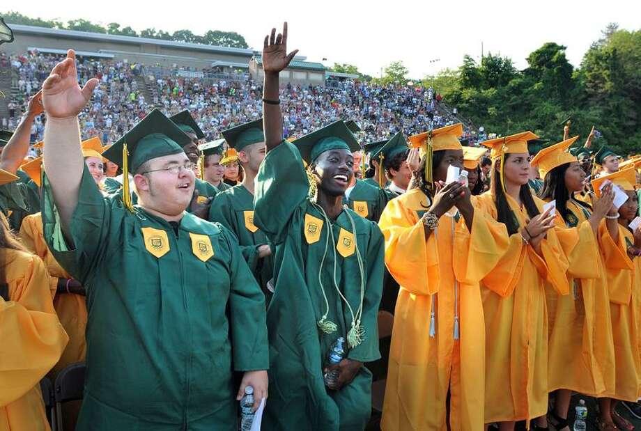 Graduates John Behler, left, and James Benjamin cheer during the Hamden High School graduation ceremonies in the school's football stadium. Peter Casolino/New Haven Register