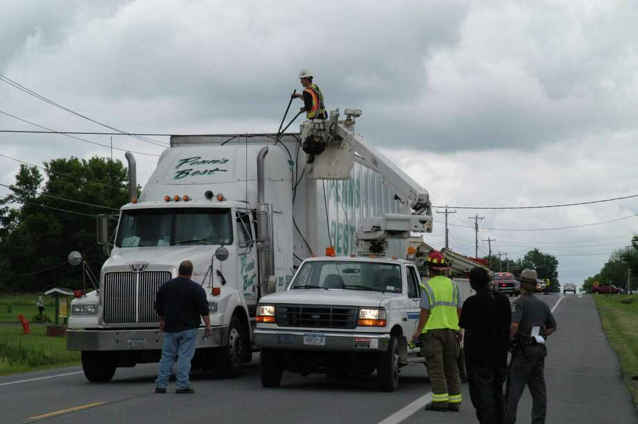 Dispatch Photo by Caitlin Traynor TDS Telecom workers cut away a telephone wire entangled with a tractor trailer on Route 31 in Verona Monday around 11:45 a.m.