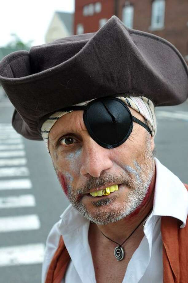"""Milford-- """"Pirate"""" Giom Grech of Cold Spring, NY, shows off his fancy teeth on River Street during the annual Captain Kidd Treasure Hunt in downtown Milford. The event, sponsored by the Milford Downtown Milford Business Assoviation, provides kids and families with """"Treasure maps"""" which leads them through downtown businesses with clues in a scavenger hunt style adventure.  Photo-Peter Casolino/New Haven RegisterCas110612   6/10/12"""