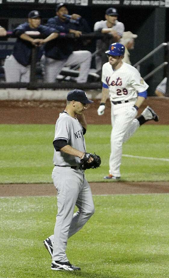 New York Yankees starting pitcher Andy Pettitte, bottom, looks on as New York Mets first baseman Ike Davis (29) heads to home plate after hitting a three-run home run during the first inning Friday night's game at Citi Field in New York. The Mets won 6-4.