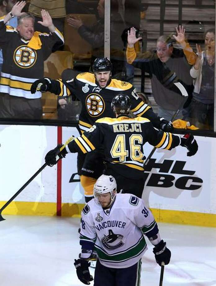 Boston Bruins left wing Milan Lucic , top, celebrates with center David Krejci after scoring, as Vancouver Canucks right wing Victor Oreskovich skates away during the first period of Game 6 of the NHL hockey Stanley Cup Finals in Boston, Monday, June 13, 2011. (AP Photo/The Canadian Press, Jonathan Hayward) Photo: AP / The Canadian Press