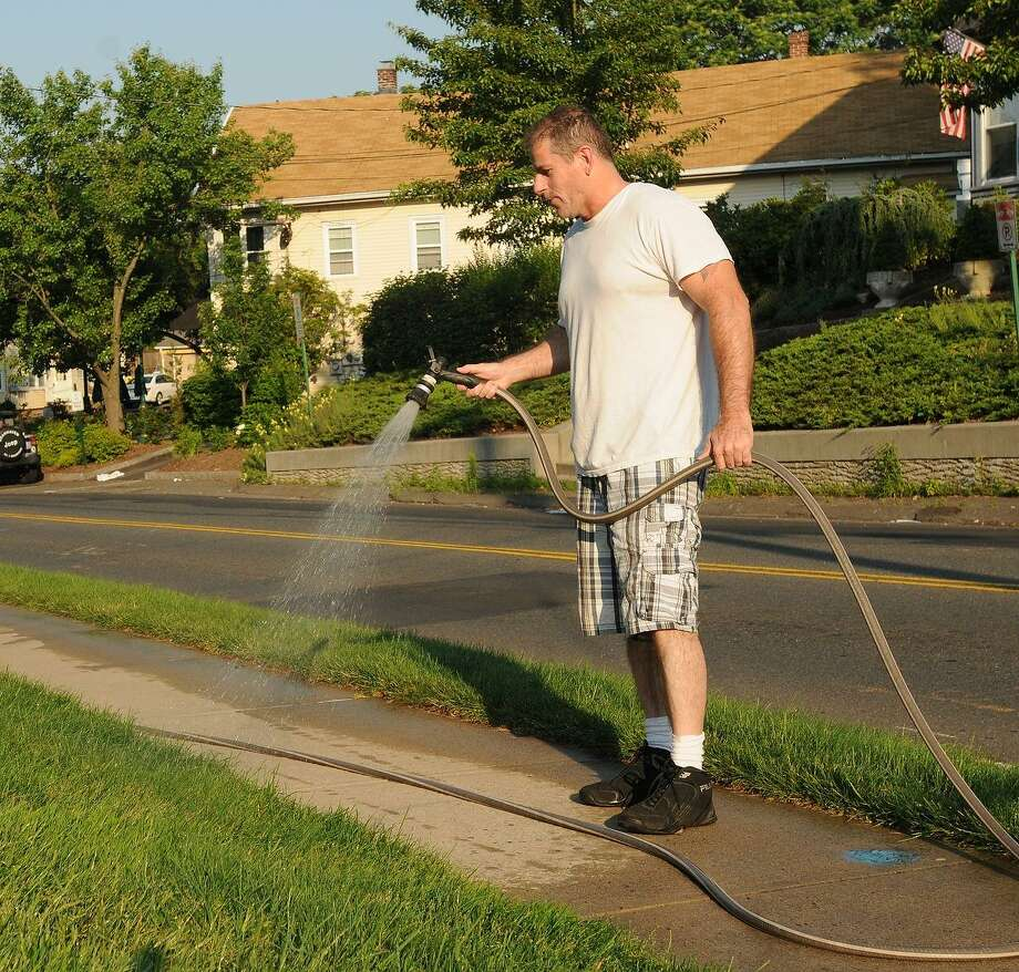 Billy Williams, fighting the heat, hydrates his front lawn early Thursday morning on East Main Street in Branford.  Peter Hvizdak/Register Photo: New Haven Register / ©Peter Hvizdak /  New Haven Register