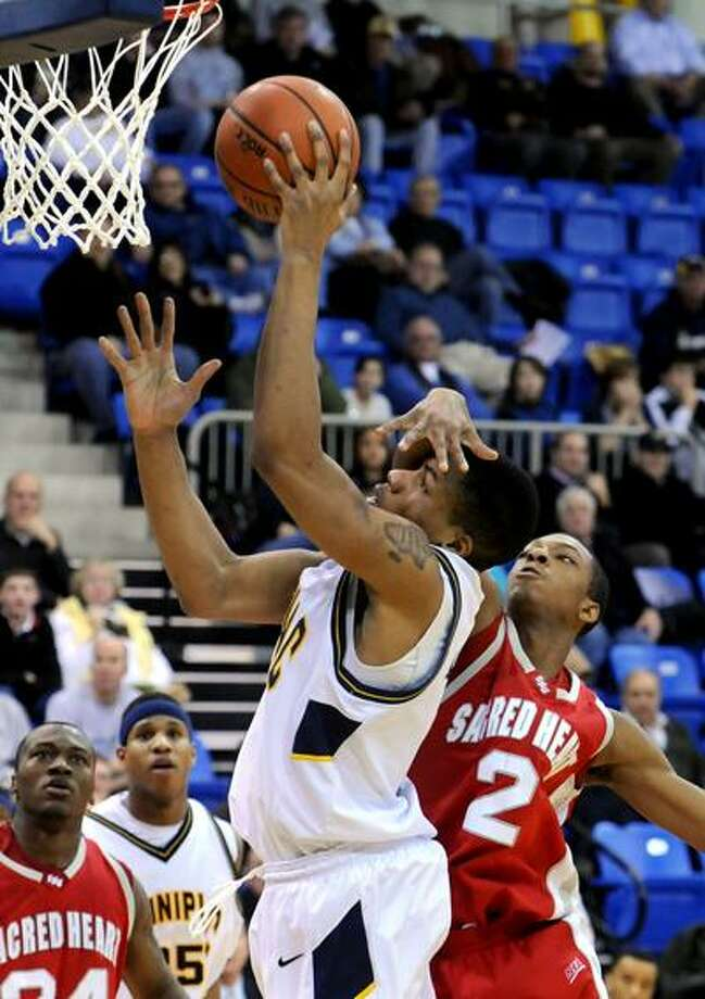 Sacred Heart University at Quinnipiac University basketball, 1st half. QU's James Johnson up for two, with SHU's Evan Kelley's hand defending. Photo by Mara Lavitt/New Haven Register2/9/11