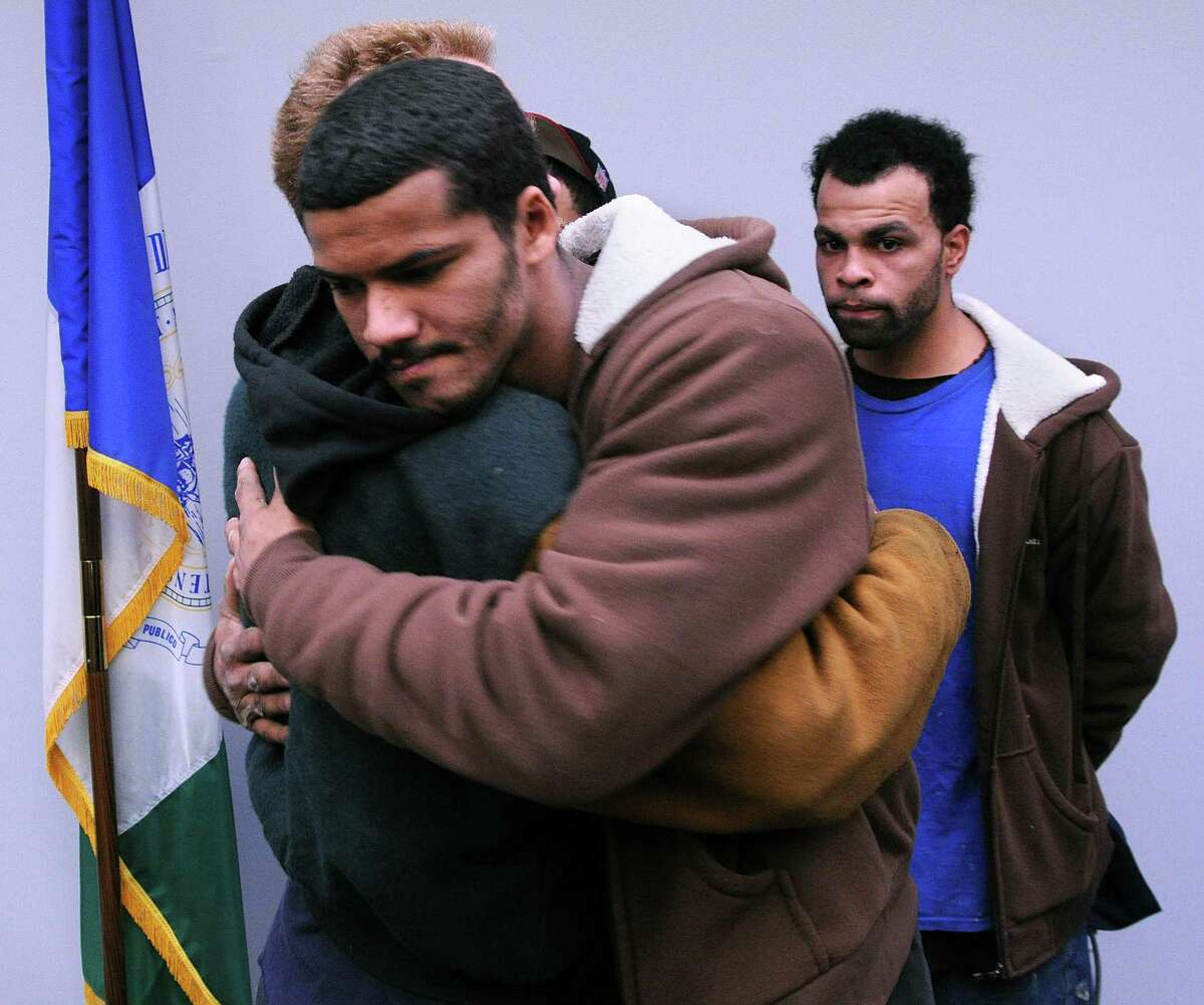 New Haven-- John Soules (facing camera) hugs his cousin Joseph Dohna following a press conference announcing an arrest warrant in the bludgeoning death of Louise Soules and Mike Mobley in 2004. Louise Soules was John Soules' mother and Dohna's aunt. Behind them is Billy Mathew, nephew of Louise Soules. Police have secured a warrant for the arrest of Charlie Levine, 59, for the killings. Levine is currently in custody in Florida for other crimes. Peter Casolino/New Haven Register12/28/11