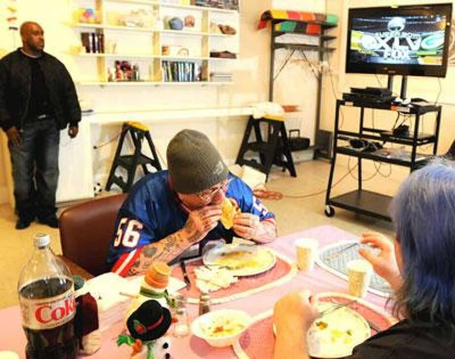 Robert Amsterdam, 53, center and Dustin Hunter, 24, right, Columbus House homeless shelter clients, eat their dinner as they watch the start of Super Bowl XLV Sunday 2/6/2011 at the North Haven Congregational Church where they will be staying overnight. The church is among a group of churches in the area who are participating in Abraham's Tent, a joint program between Interfaith Cooperative Ministries and Columbus House to help overcrowding at  New Haven's overflow shelters. The churches take in 12 homeless men each week. (Photo by Peter Hvizdak/Register)
