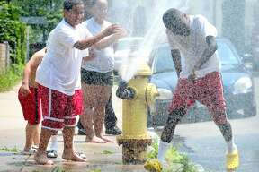 Kevin Wilfong, 11, right, runs through the water coming out of a sprinkler on a fire hydrant on Button Street in New Haven. At left is Christopher Carrero, 11. Photo by Arnold Gold/New Haven Register