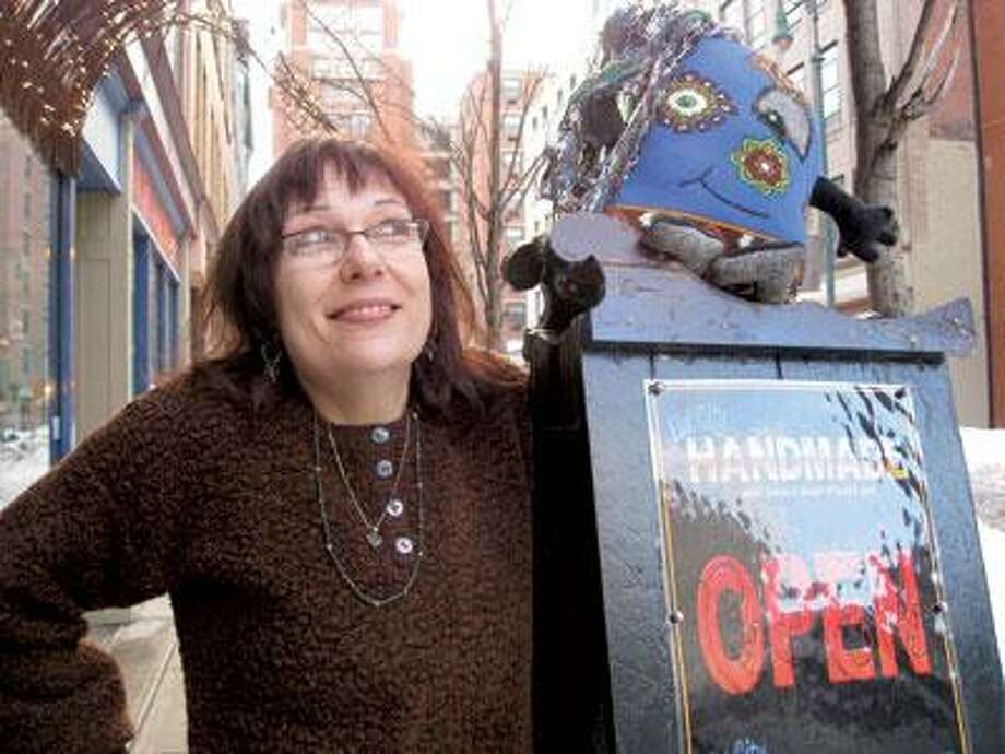 """Lisa Spetrini, director of Elm City Handmade, hopes the space in Ninth Square becomes a place where curious and creative types can meet. For Dollwars, artists and nonartists alike are invited to submit """"pillow people"""" and other creatures for a competition on Saturday. (Sandi Kahn Shelton/Register)"""