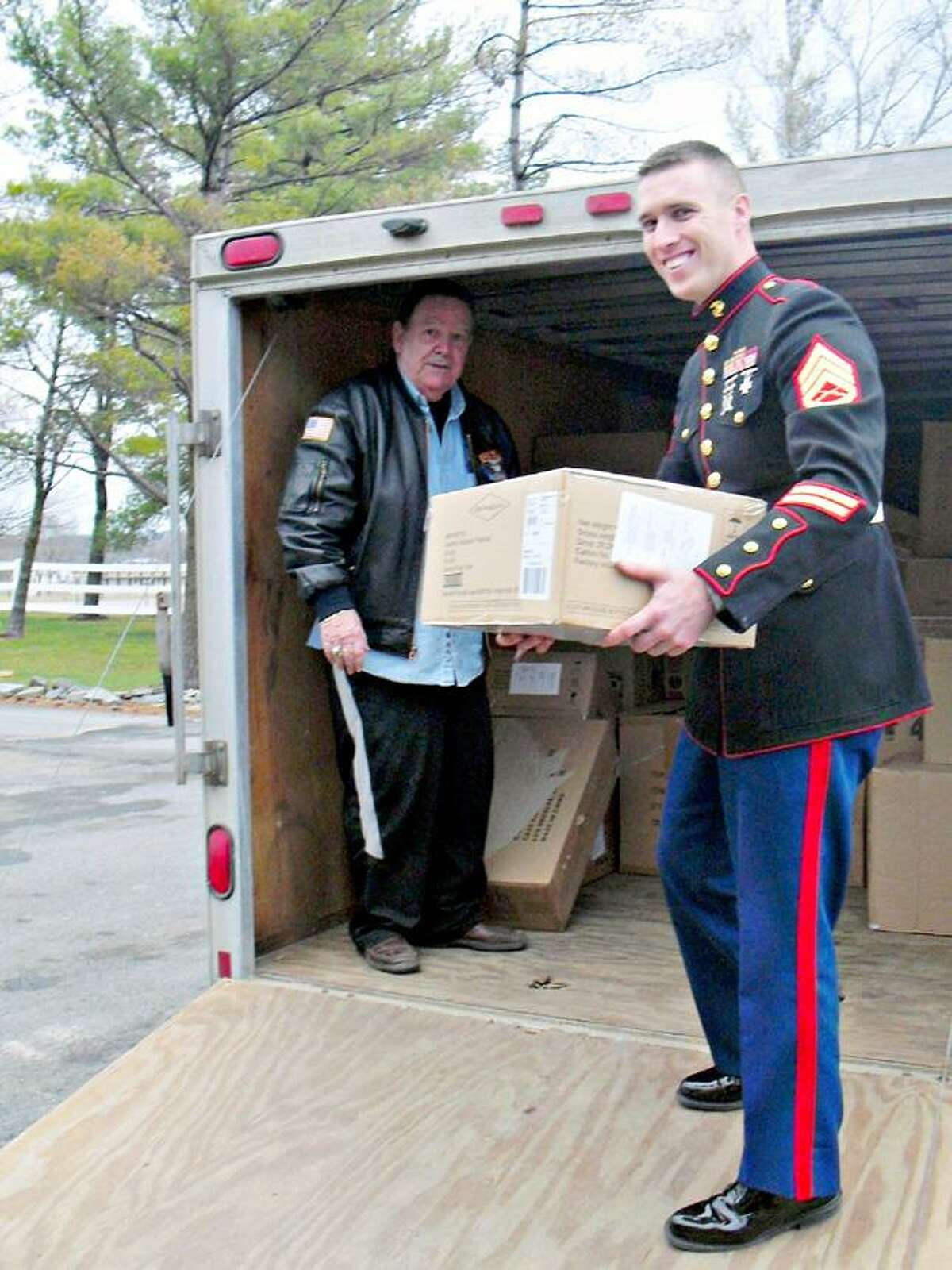 Photo Courtesy VERNON DOWNS A representative from the Syracuse-area Toys for Tots and a member of the U.S. Marine Corps load toys onto a truck at Vernon Downs.