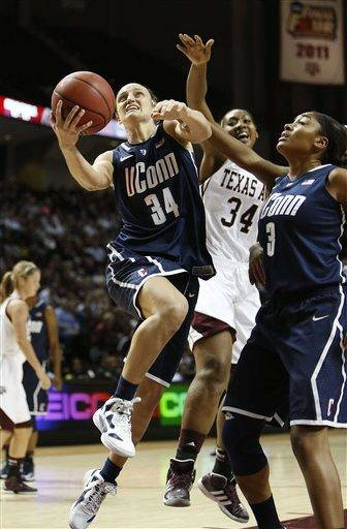 Connecticut's Kelly Faris (34) shoots the ball against Texas A&M defender Karla Gilbert (34) during the second half of an NCAA college basketball game on Sunday, Nov. 18, 2012, in College Station, Texas. Connecticut won 81-50. (AP Photo/Jon Eilts)