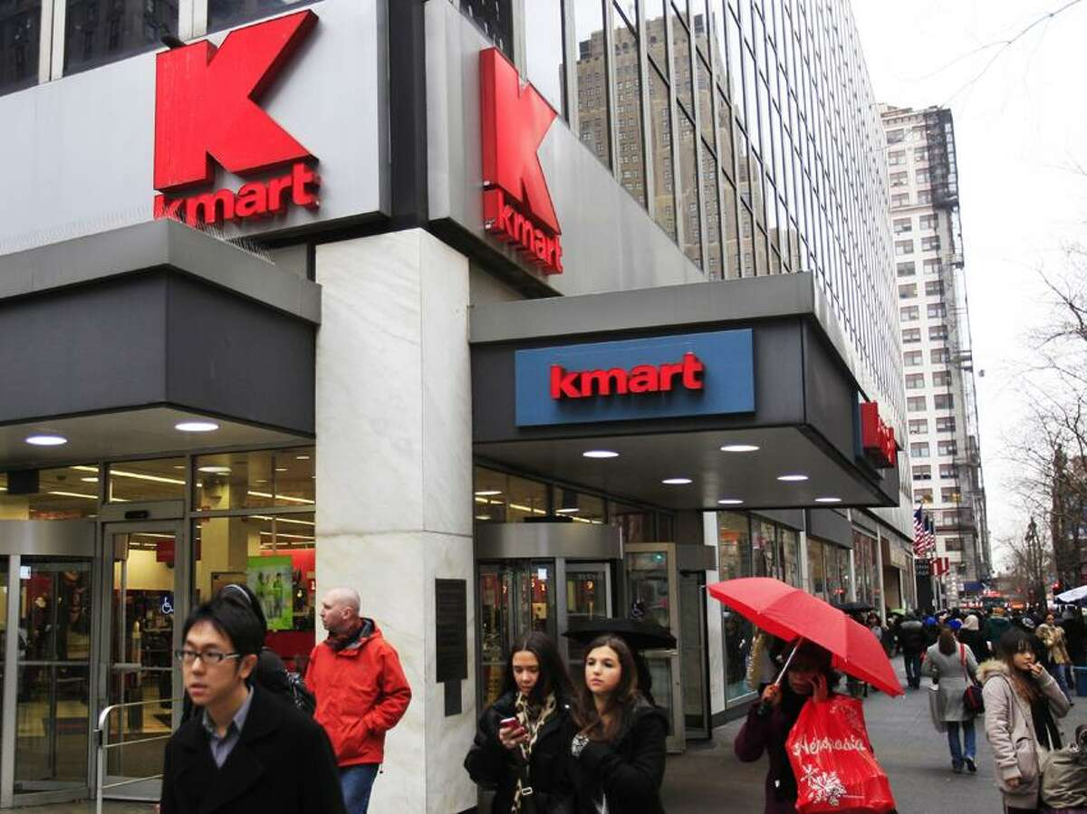 Pedestrians pass a Kmart location in New York. Sears Holdings Corp., the parent company of Sears and Kmart department stores, announced Tuesday that it will close 100 to 120 stores after a sluggish holiday season.(Associated Press)