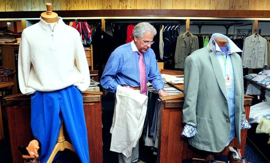 Jim Civitello, president of Enson's menswear store in New Haven, hangs pants in the store Monday. Consumers plan to spend more on the upcoming Father's Day holiday this year - at places including specialty clothing shops - than in recent years. (Photo by Arnold Gold/New Haven Register)