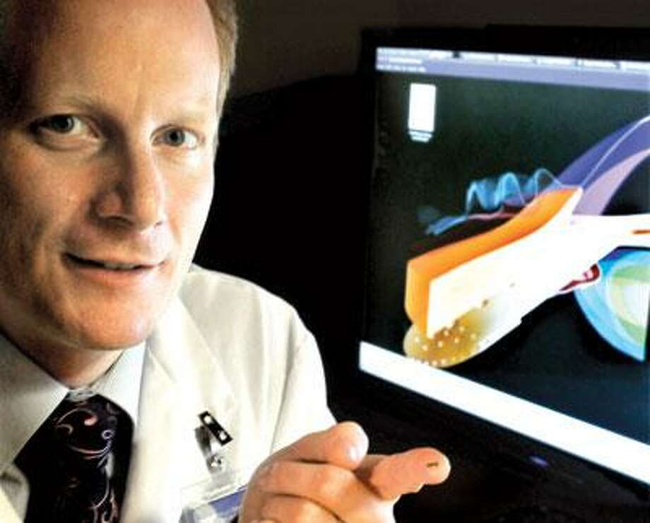 Dr. Nils Loewen of the Yale Eye Center shows a gold shunt used in glaucoma treatment, on his fingertip. The tongue-shaped shunt, with small holes to allow for drainage, can be seen in the illustration behind Loewen. (Melanie Stengel/Register)
