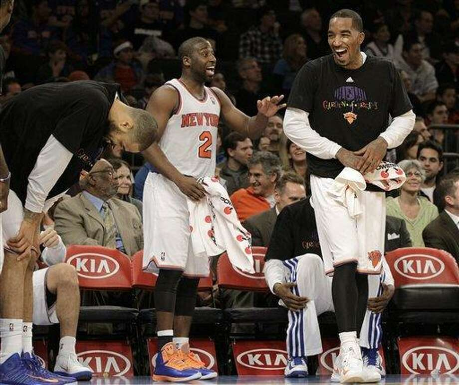 From left, Tyson Chandler, (bent over) Raymond Felton (2) and J.R. Smith react after watching bench player Chris Copeland complete a dunk in the final seconds of the fourth quarter of the Knicks 88-76 victory over the Indiana Pacers in their NBA basketball game at Madison Square Garden in New York, Sunday, Nov. 18, 2012. Most of the starting lineup were on the bench by then.  (AP Photo/Kathy Willens) Photo: AP / AP