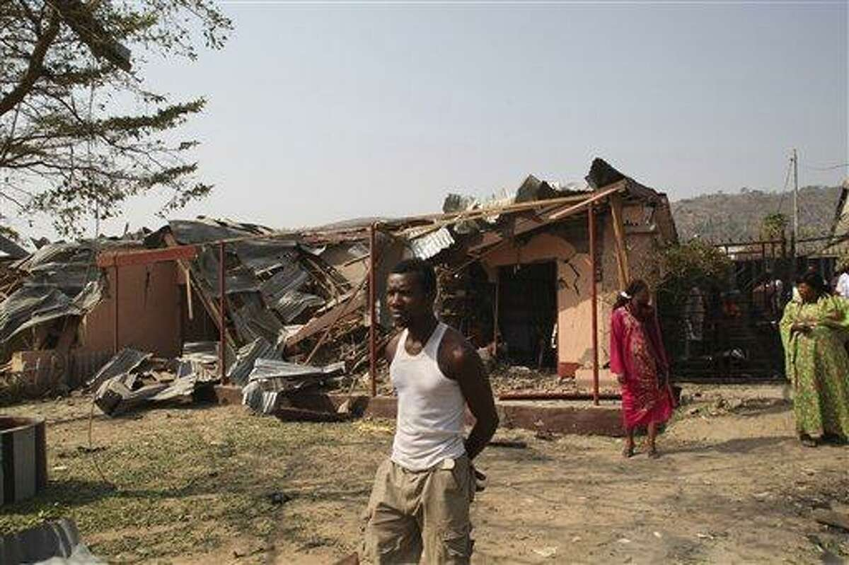 An Unidentified man stand in front of a destroyed building at the site of a bomb blast at St. Theresa Catholic Church in Madalla, Nigeria, Sunday, Dec. 25, 2011. An explosion ripped through a Catholic church during Christmas Mass near Nigeria's capital Sunday, killing at least 25 people, officials said. A radical Muslim sect claimed the attack and another bombing near a church in the restive city of Jos, as explosions also struck the nation's northeast.(AP Photo/Sunday Aghaeze)