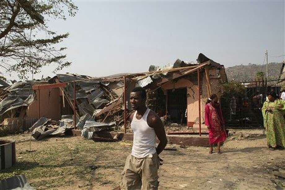 An Unidentified man stand in front of a destroyed building at the site of a bomb blast at St. Theresa Catholic Church in Madalla, Nigeria, Sunday, Dec. 25, 2011. An explosion ripped through a Catholic church during Christmas Mass near Nigeria's capital Sunday, killing at least 25 people, officials said. A radical Muslim sect claimed the attack and another bombing near a church in the restive city of Jos, as explosions also struck the nation's northeast.(AP Photo/Sunday Aghaeze) Photo: AP / AP