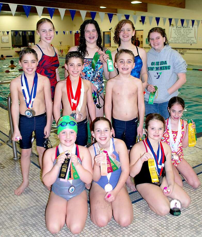 Submitted Photo Oneida YMCA Dolphins swim team members pose with medals from a meet on December 17 at RIT. The team is, from left, (front) Hannah Kellogg 8, Bailey Simmons 9, Darien Tompkins 8, (middle) Aidan Hicks 8, Ajay Hicks 8, Drew Hicks 6, Mattie Hicks 8, (back) McCailin O'Rourke, Olivia Caroli 11, Maggie Cummings and Paige Snell. Local swimmers on the Clinton Cudas swim team had a meet the same day in Saratoga Springs
