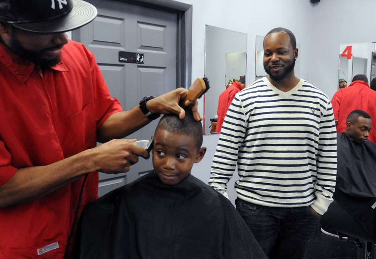 """Barber Troy Walters, left works on Quandre Henry, 4, as Headz Up Barber Shop owner Greg """"Chanz"""" Simpkins, right, looks on. All are from New Haven. Mara Lavitt/Register"""