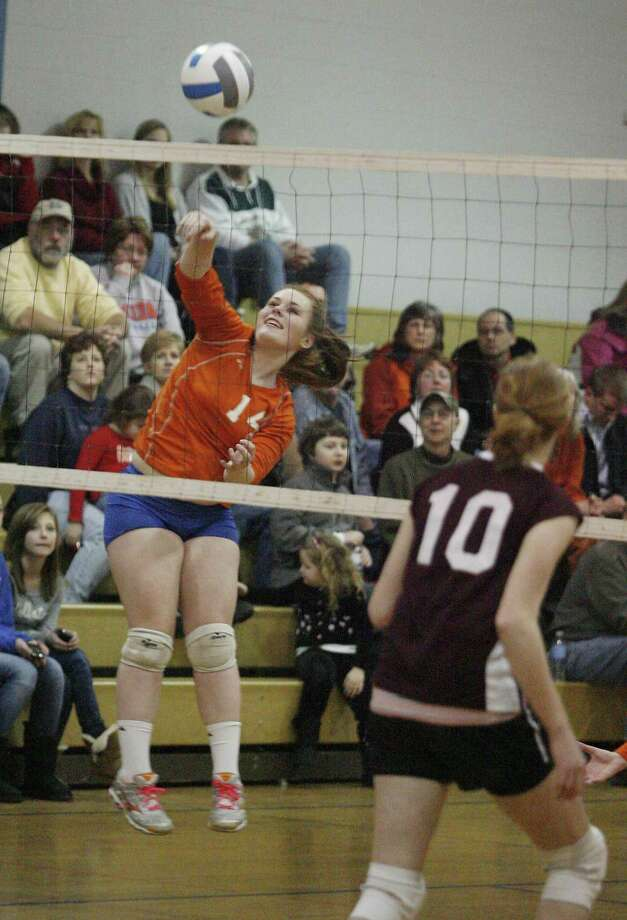 Dispatch Staff Photo by JOHN HAEGER Oneida's Shannon Dowling (14) puts a shot over the net as Clinton's Kait Christ  (10) reacts in the second game of the match in Oneida on Friday, Feb. 4, 2011
