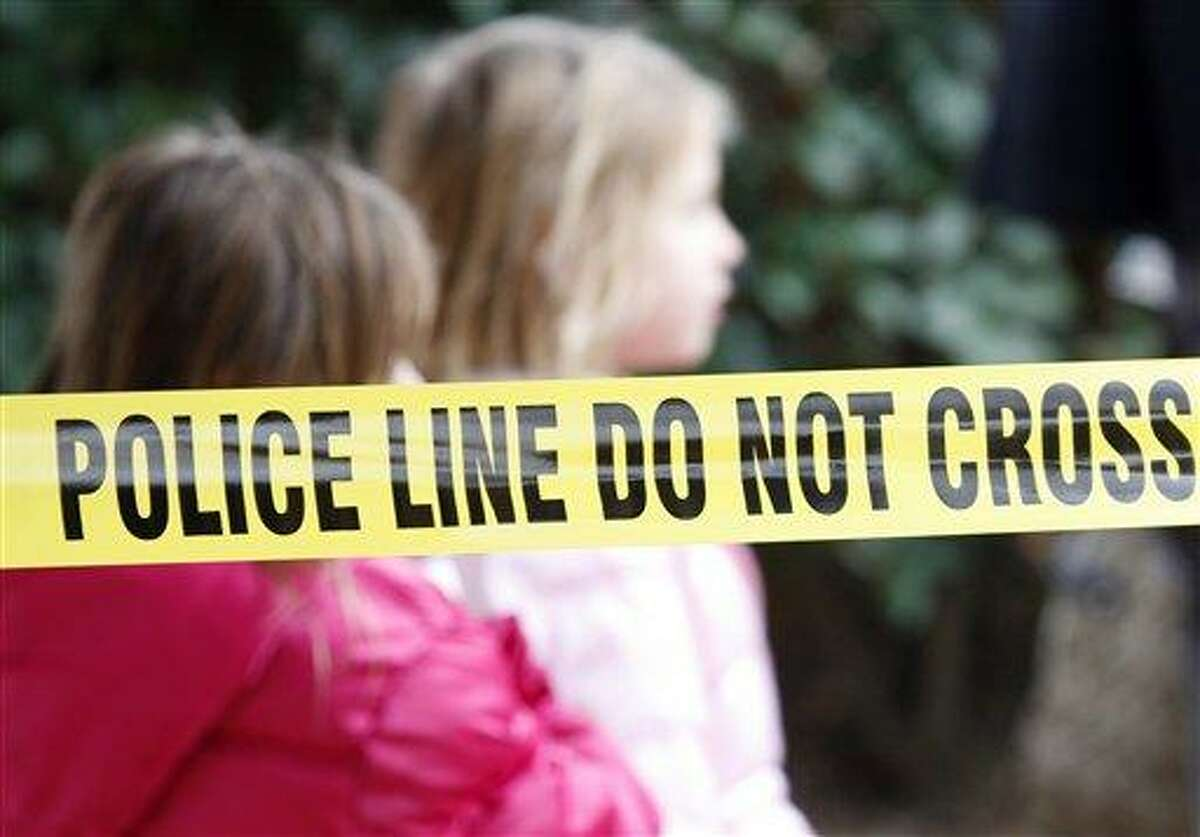 Two young girls walk by police tape that stretches through a Grapevine, Texas, apartment complex where police found seven people dead in an apartment on Sunday, Dec. 25, 2011 in Grapevine, Texas. Four women and three men who police believe to be related were found apparently shot to death, and authorities said they believe the shooter is among the dead. (AP Photo/Mike Fuentes)