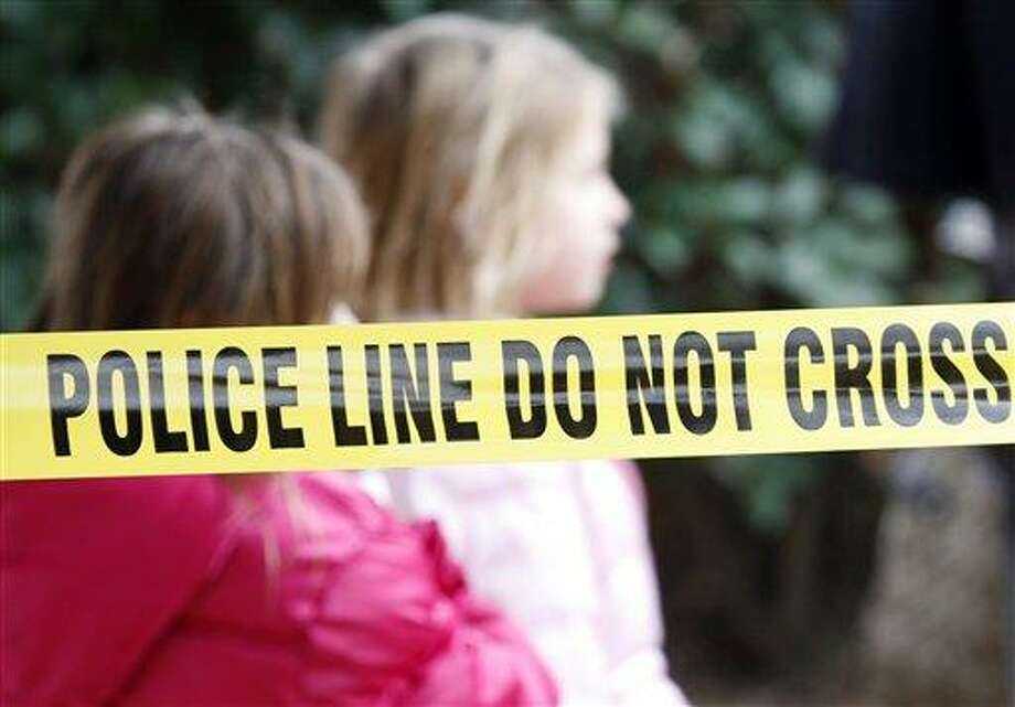 Two young girls walk by police tape that stretches through a Grapevine, Texas, apartment complex where police found seven people dead in an apartment on Sunday, Dec. 25, 2011 in Grapevine, Texas. Four women and three men who police believe to be related were found apparently shot to death, and authorities said they believe the shooter is among the dead. (AP Photo/Mike Fuentes) Photo: ASSOCIATED PRESS / AP2011
