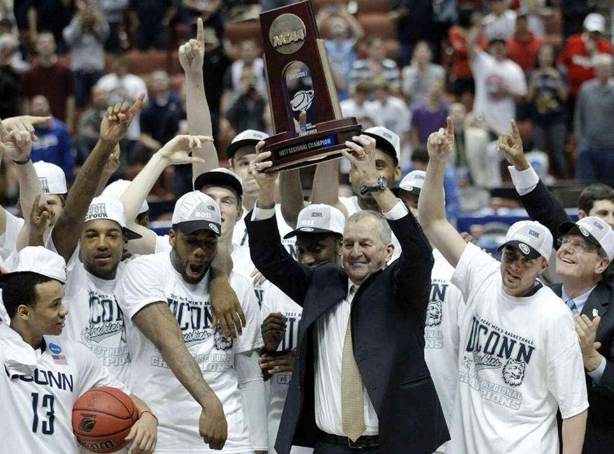 The sight of UConn men's basketball coach Jim Calhoun hoisting a championship trophy was the Register's No.1 sports story. The Huskies, who are shown celebrating their NCAA West regional title, went on to win the national championship at the Final Four (AP photo).