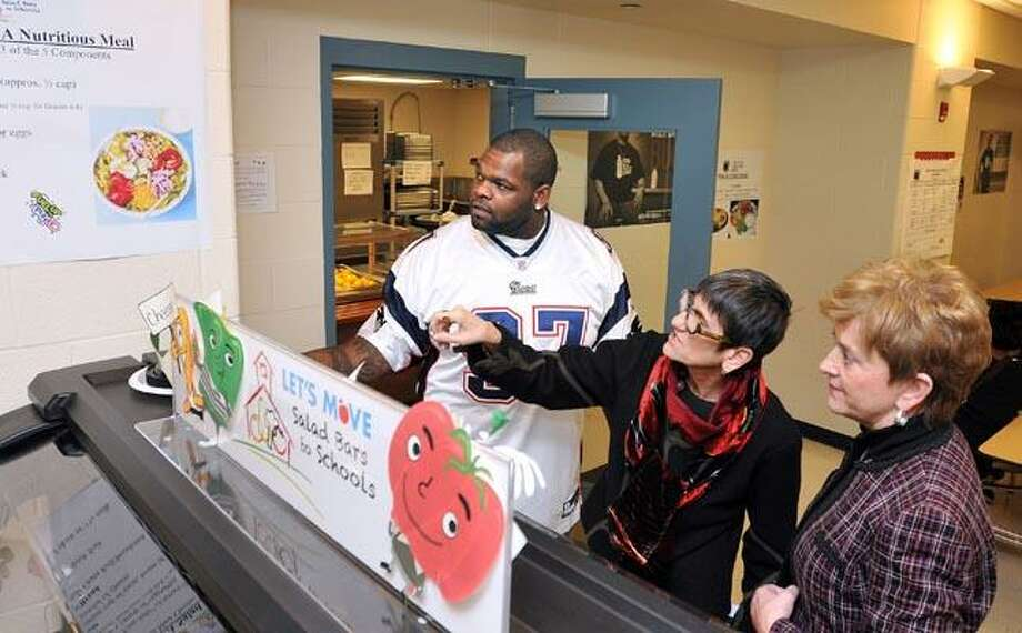 "New England Patriots Defensive Lineman Ron Brace chats with Congresswoman Rosa DeLauro, center, and US Department of Agriculture Under Secretary Dr. Janey Thronton at the new salad bar at the Mauro-Sheridan Science, Technology and Communications School. The three were at the school promoting the ""Let's Move Salad Bars To Schools Program."" Brace spoke with a select group of students about eating healthy. (Photo by Peter Casolino/New Haven Register)  02/03/11 Cas110203"