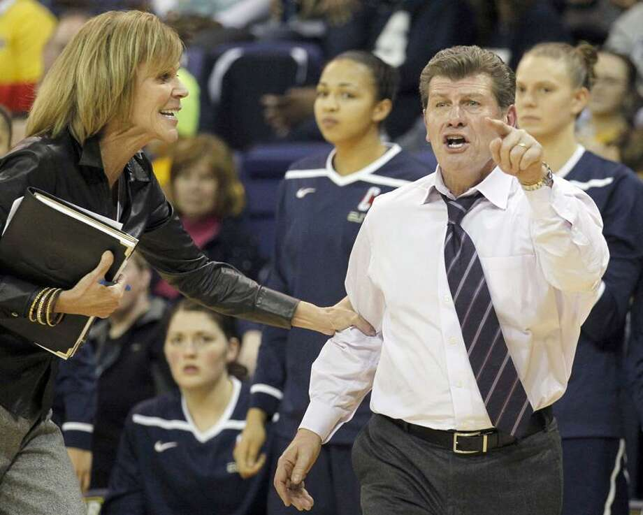 Connecticut associate head coach Chris Dailey, left, grabs head coach Geno Auriemma as he reacts in the second half of an NCAA college basketball game against Marquette on Saturday, Feb. 25, 2012, in Milwaukee. (AP Photo/Jeffrey Phelps) Photo: AP / FR59249 AP